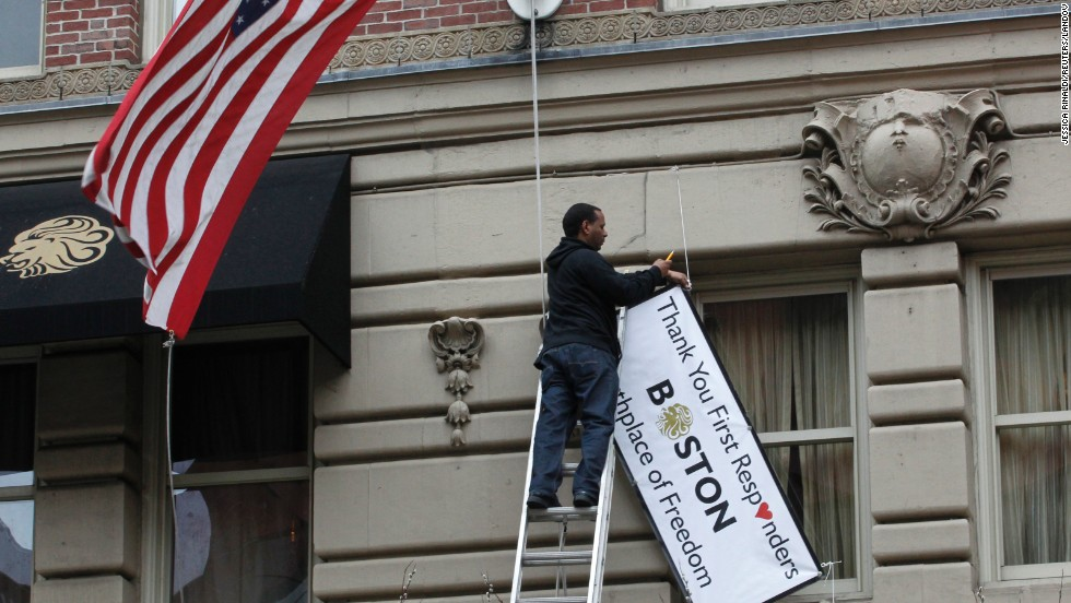 A man removes a sign hanging from the Lennox Hotel along Boylston Street after the street reopened to the public for the first time since the Boston Marathon bombings in Boston on Wednesday, April 24. The city is trying to return to normal less than a week after two bombs exploded near the finish line of the Boston Marathon, shocking the nation and leaving the city on edge. <a href='http://www.cnn.com/SPECIALS/us/boston-bombings-galleries/index.html'>See all photography relating to the Boston bombings.</a>