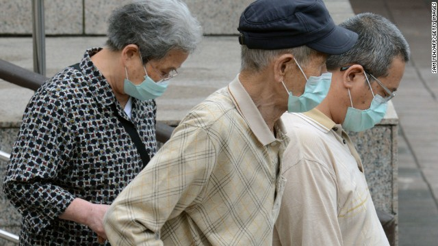 Three people wearing masks walk outside the National Taiwan University Hospital in Taipei on Thursday, April 25. China has reported 83 cases of H7N9 avian influenza.