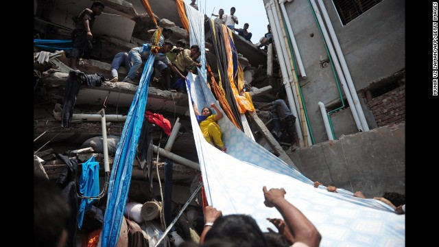 Bangladeshi garment workers help evacuate a survivor by using a roll of fabric on April 24.