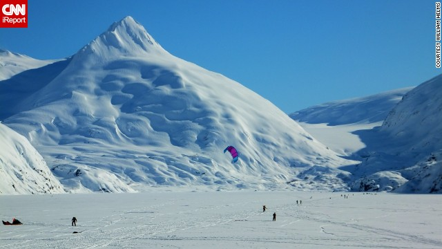 Kite skiers and cross-country skiers enjoy frozen Portage Lake near Anchorage, Alaska.