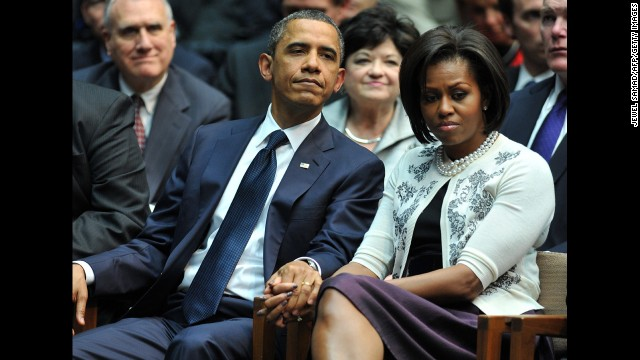 The president and first lady hold hands during a memorial service for the victims of the Tuscon, Arizona, shooting. On January 8, 2011, Jared Lee Loughner shot six people and wounded 13 more, including then-Rep. Gabrielle Giffords.
