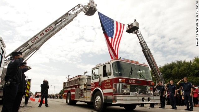 Firefighters salute as fire trucks and emergency vehicles pass under a flag before the memorial service on April 25.