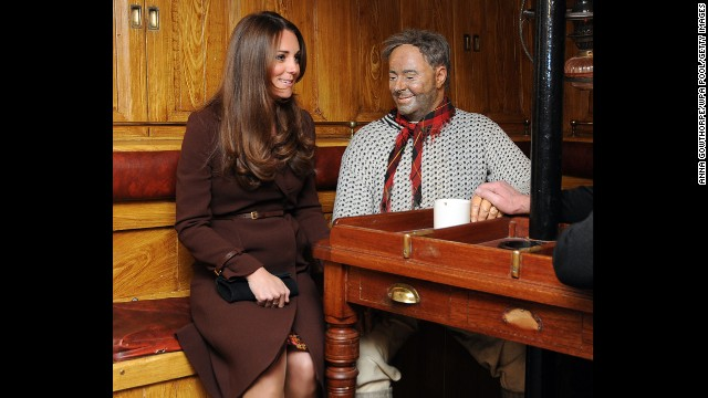 Catherine sits next to a dummy of the ship's mate at the Skipper's Table during her tour of the National Fishing Heritage Center, in Grimsby, England.