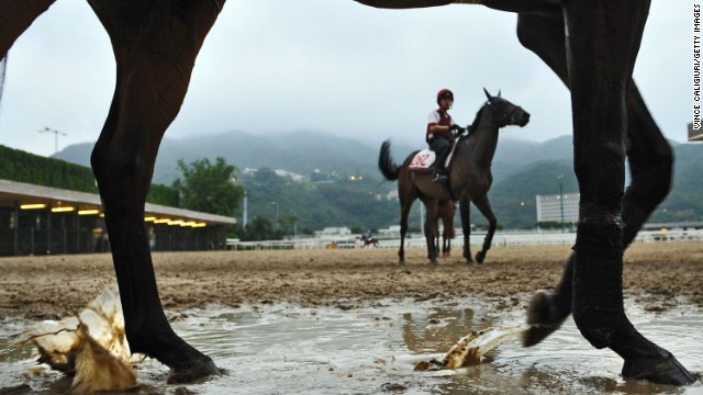 Horses and jockeys return to stables in damp weather at the Sha Tin Racecourse in Hong Kong on Friday, April 26. Preparations are under way for the upcoming Audemars Piguet Queen Elizabeth II Cup. 