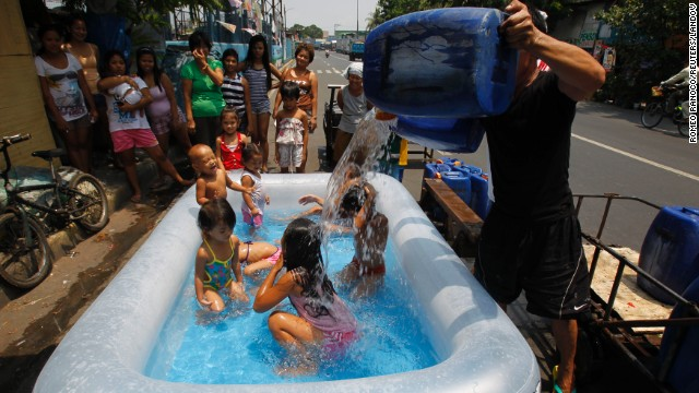 A man pours water over children swimming in an inflatable swimming pool to beat the heat in Manila, Philippines, on Friday, April 26.