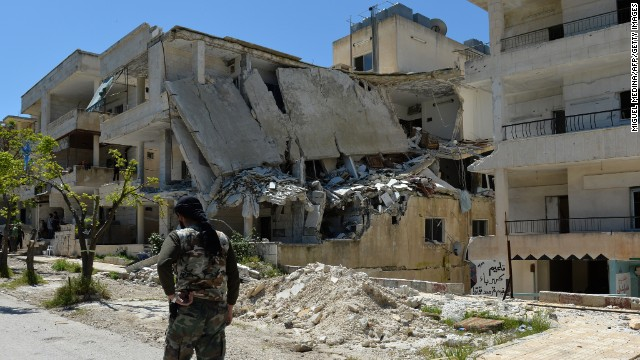 A Syrian rebel walks past a destroyed building in Salma in the coastal province of Latakia on Friday, April 26.
