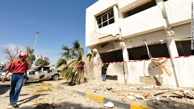 A man walks past a police station after a bomb explosion in Benghazi, Libya on Saturday.