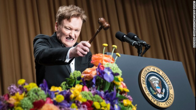 Conan O'Brien bangs a small gavel on the podium during his performance.