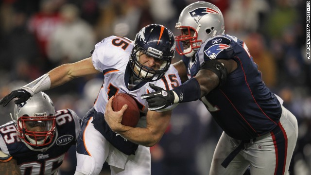 Tebow, then playing for the Denver Broncos, runs the ball against Mark Anderson, left, and Brandon Deaderick of the New England Patriots during an AFC divisional playoff game in January 2012 in Foxborough, Massachusetts.