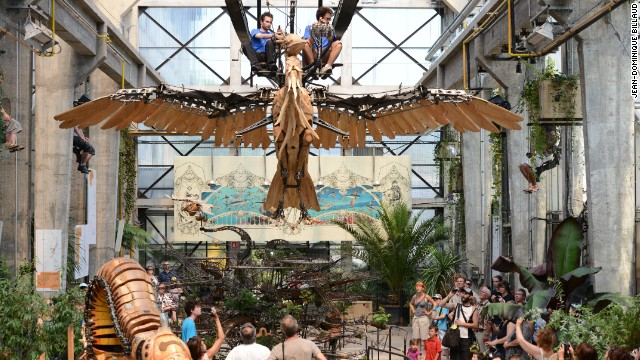 Two people ride a mechanical bird at a French themepark.