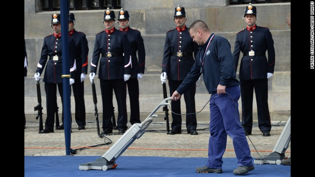 A cleaner vacuums the carpet outside the Royal Palace during Queen Beatrix's abdication ceremony.