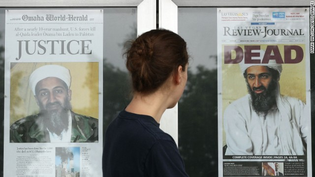 A passer-by looks at newspaper headlines in front of the Newseum in Washington.