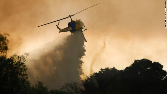 A helicopter makes a water drop next to a small fire tornado near Camarillo.