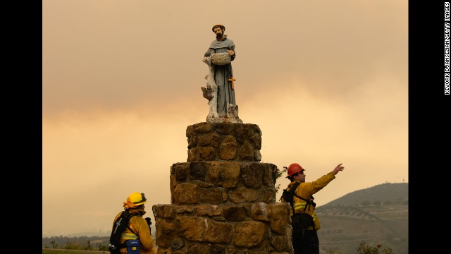 San Bernardino County firefighters observe the wildfire next to a statue of St. Francis of Assisi on May 3 in Hidden Hills, California. Thousands of homes are threatened by the growing wildfire northwest of Los Angeles that has forced the closure of the scenic coastal highway.