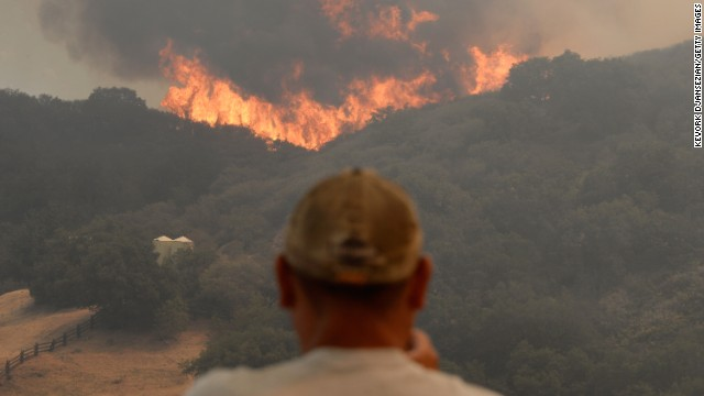 A man takes a photo of the wall of flames on May 3 in Hidden Hills.