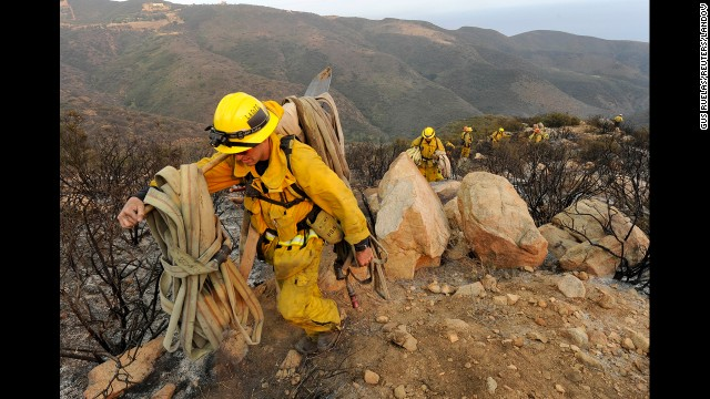 Firefighters make their way out of a canyon near Malibu, California, on May 3.