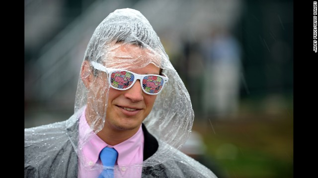 A race fan dons a plastic poncho to ward off the rain.
