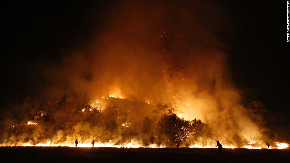 Firefighters start a backfire into the Santa Monica Mountains to help control the Springs Fire in southeast Ventura County, California, on Saturday, May 4. The fire damaged 15 homes and five commercial properties and destroyed 25 outbuildings in the Los Angeles area as of Saturday, fire authorities said.