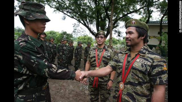"Pacquiao shakes hands with a Special Forces Operation Course student during the 49th Special Forces Regiment anniversary at Fort Magsaysay in Nueva Ecija, north of Manila, on June 27, 2011. During the event, Pacquiao received the Honorary Special Forces Warrior Badge, and wore the exclusive Special Forces uniform popularly known as the ""Tiger suit."""