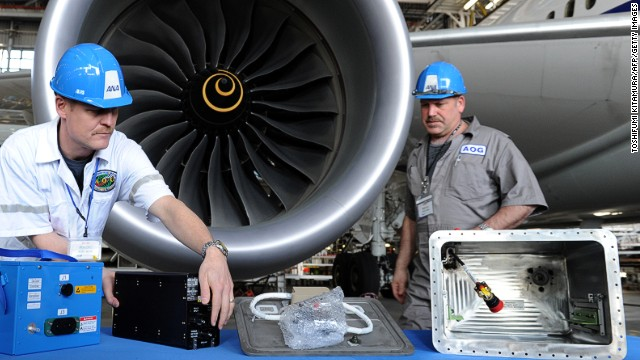 Members of Boeing's Aircraft On Ground (AOG) team display components of the new Dreamliner battery system after an ANA 787 test flight late last month. To implement the fix, Boeing moved a small army of technicians to 13 international locations.