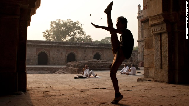 MAY 07 - NEW DELHI, INDIA: Om Dubey, 20, shows off his moves as elderly yoga practitioners sit in the courtyard of a mosque. India's under-30s, comprising 60% of its 1.2 billion population, represent what experts call the