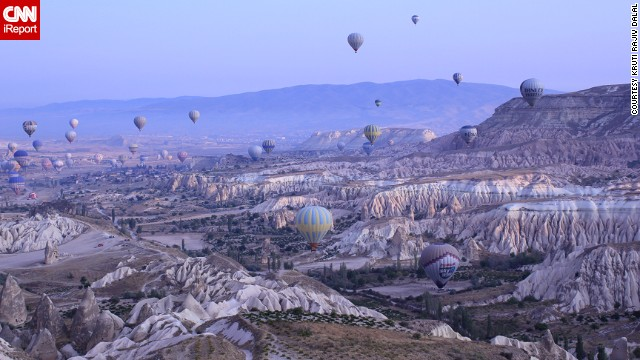 Hot air balloons float over the otherworldly valleys of Cappadocia at dawn.