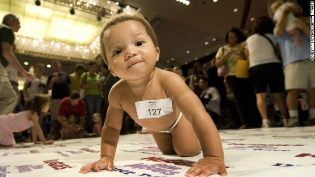 A diaper-clad baby crawls across a 10-foot mat during a baby race in New York. The first prize was a year's supply of diapers.
