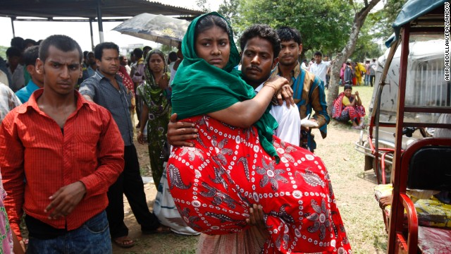 An injured worker who survived the building collapse is carried by her husband to collect her wages in Savar near Dhaka, Bangladesh, on Wednesday, May 8.