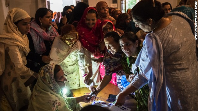 Pakistani women jostle to receive their ballot papers prior to casting their ballot at a polling station on May 11, in the Old City of Lahore, Pakistan.