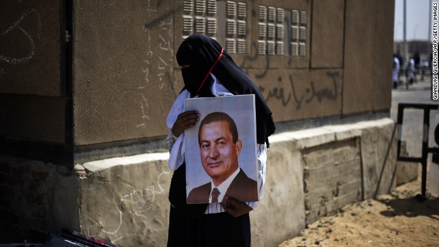 MAY 11 - CAIRO, EGYPT: A supporter of former Egyptian president Hosni Mubarak holds his portrait outside the Egyptian police academy in Cairo, on the first day of the retrial on May 11, 2013. Mubarak is appealing against his conviction for the murder of hundreds of peaceful protesters during the 2011 uprising.