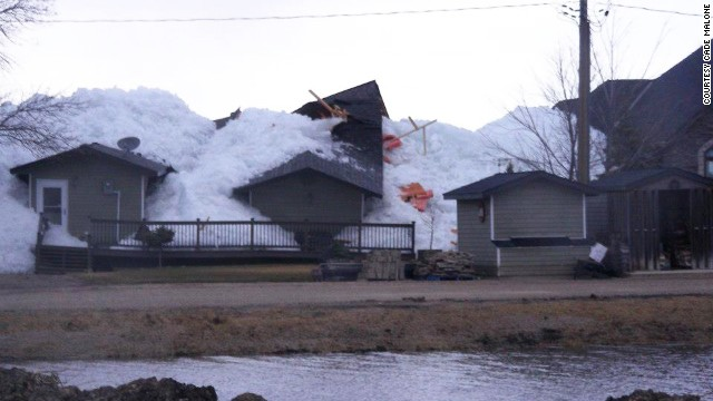 Ice sheets pushed ashore by winds destroyed homes in Manitoba, Canada, over the weekend. Pictured, a house is overcome by the ice sheet on Sunday, May 12.