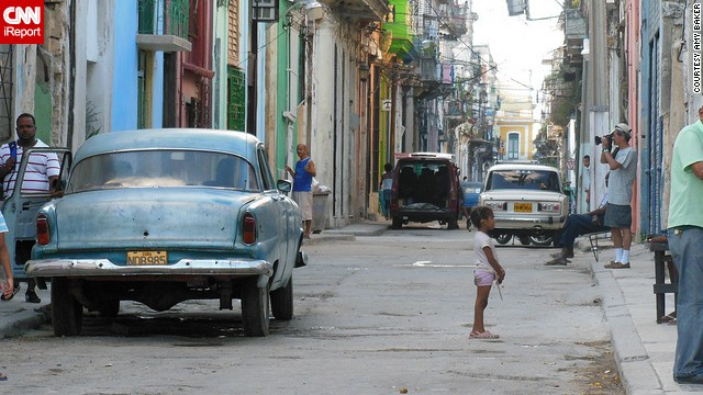 A little girl waits for her playmate in the vibrant streets of Havana, Cuba.