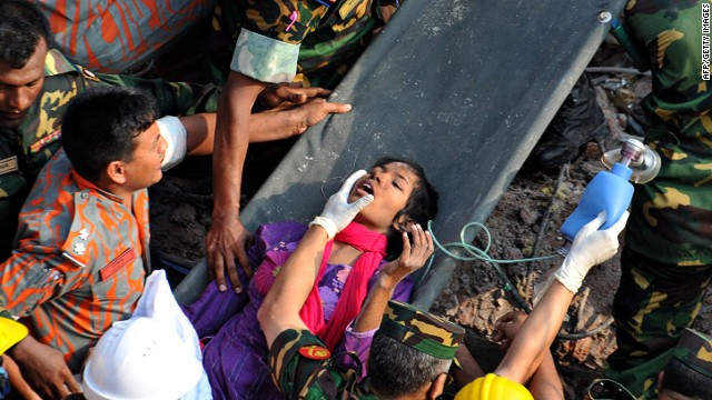 Rescuers workers administer first aid as they carry Begum from the rubble on May 10 in Dhaka.
