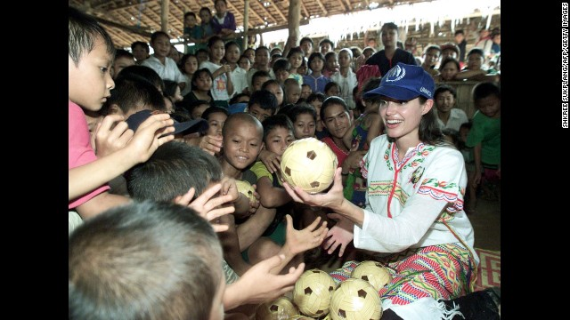 Jolie distributes balls to the children at the Tham Hin refugee camp on the Thai-Myanmar border in May 2002. She is a goodwill ambassador for the United Nations high commissioner for refugees.