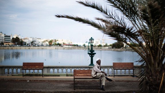 A man sits on a bench next to an artificial lake between the waterfront and Tripoli's iconic Martyrs' Square, formerly Green Square, on October 5, 2011.