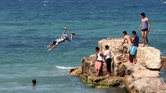 A young man jumps into the waters of the Mediterranean Sea, off the coast of Tripoli on April 30, 2012.