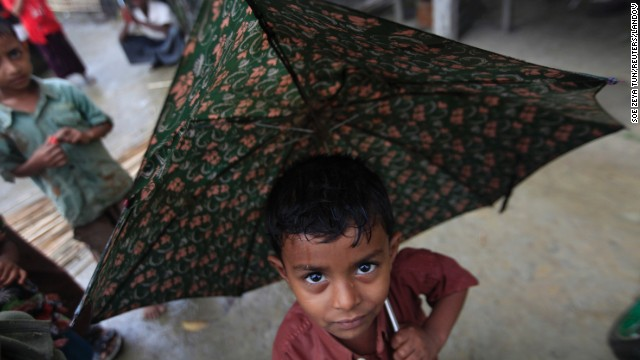 A boy from Thandawli shelters himself from the rain in the Rohingya camp near Sittwe on May 14.