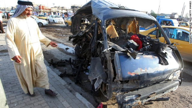 An Iraqi man looks at the remains of a vehicle at the scene of a car bomb explosion in Baghdad's Sadr City district.