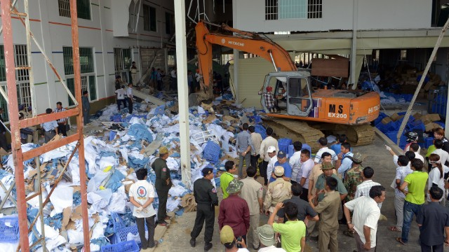 Cambodian rescue team and soldiers look for workers who may have been trapped by the walkway collapse at the Wing Star Shoe Co. factory on May 16.