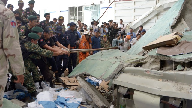 Cambodian soldiers try to move concrete after a walkway collapsed in a shoe factory warehouse in Kampong Speu province, west of Phnom Penh, on Thursday, May 16. Two people died and six were injured after the raised concrete walkway fell.