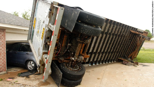 A trailer rests against a garage in Cleburne on May 16 after being blown into a house.
