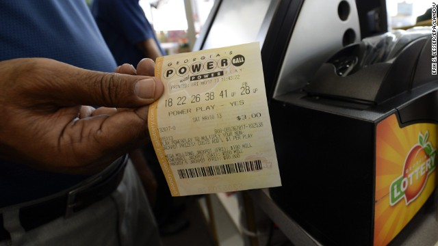 A retailer holds a Powerball lottery ticket at a store in Decatur, Georgia, on Friday, May 17. The multistate Powerball jackpot was $590.5 million, with a cash value of $376.9 million, according to the Multi-State Lottery Association.