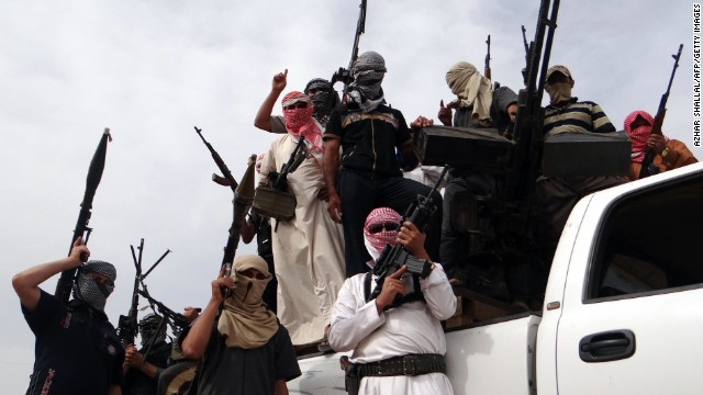 Iraqi armed tribesmen pose for a picture on the back of a truck in a road north of Ramadi on May 18.