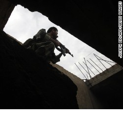 A Syrian army soldier inspects a house in the village of Western Dumayna, 7 km north of the rebel held city of Qusayr on May 13, 2013. 
