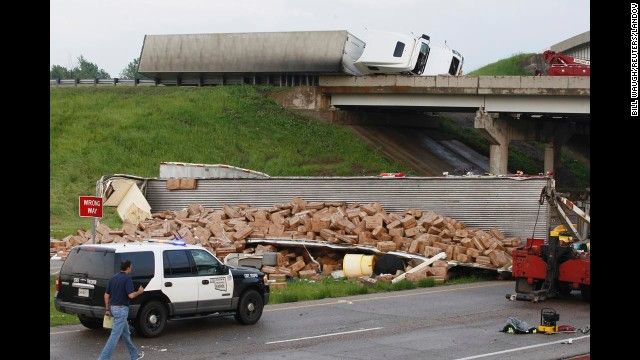 A tractor-trailer lies on its side on Interstate 40 while another is broken open on the road below after falling from the overpass after a tornado strike near Highway 177 north of Shawnee on May 19.