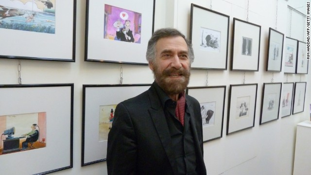 Syrian artist Ali Farzat at an exhibition of his cartoon paintings. Protesters and rebels alike have carried printouts of his work.