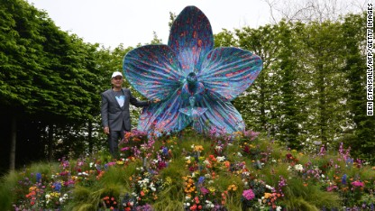 British artist Marc Quinn poses with his sculpture of an orchid in the Royal Horticultural Society (RHS) garden during the Chelsea Flower Show press day in London on May 20, 2013. The world-famous gardening event run by the Royal Horticultural Society (RHS) is celebrating its centenary year. AFP PHOTO / BEN STANSALL (Photo credit should read BEN STANSALL/AFP/Getty Images)
