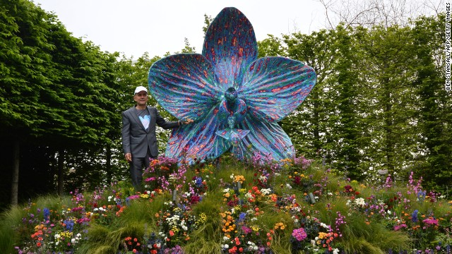 British artist Marc Quinn poses with his sculpture of an orchid in the Royal Horticultural Society garden on May 20, 2013. The world-famous gardening event is celebrating its centenary year.