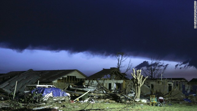 As dawn breaks, storm clouds roll in over a devastated neighborhood in Moore on May 21.