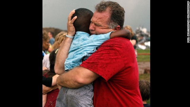 Jim Routon hugs his neighbor, 7-year-old Hezekiah, after the tornado strikes on May 20. An earlier version of this caption incorrectly stated that Routon was Hezekiah's teacher. See an interview with the pair.